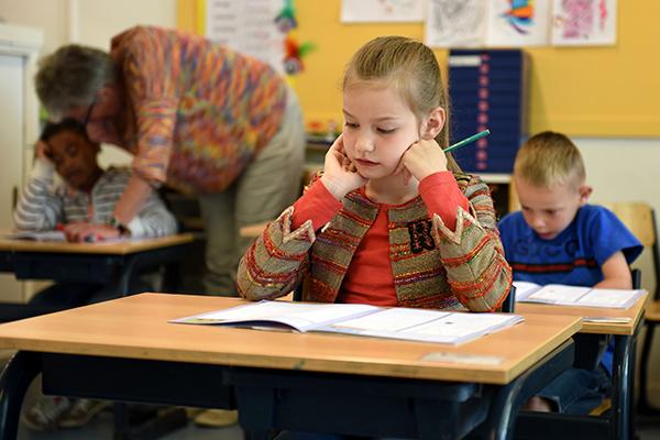 children sitting at desk in class