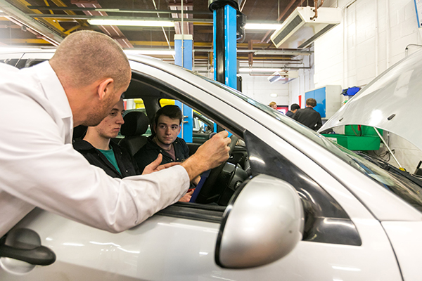 student and lecturer in a car in the college workshop