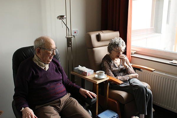 two elderly people sat in chairs in a nursing home