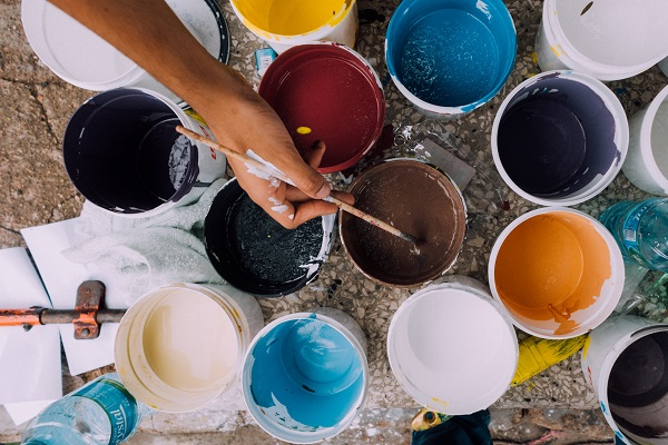 pots of different coloured paint on the floor with someone dipping their paintbrush in one