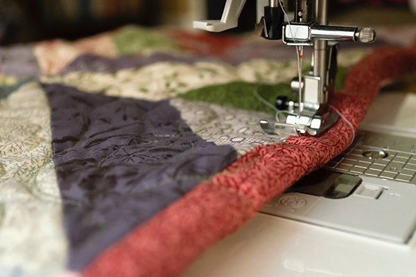 close up of fabric going through a sewing machine
