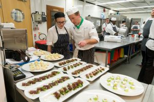 Image of a lecturer and student chef in the kitchen working with food