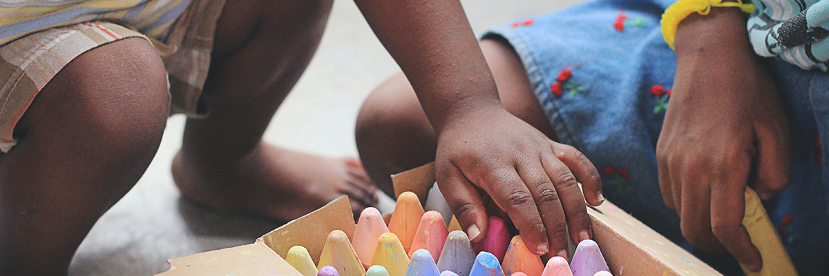 child playing with pastel crayons