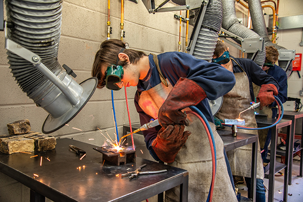 student working at a bench in engineering workshop wearing protective eyewear