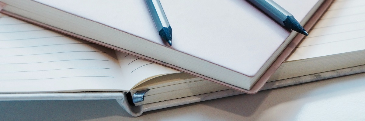close up of a pen on some notebooks