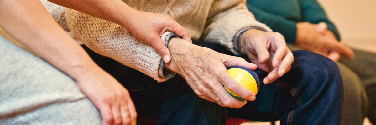 close up of an elderly persons hands with someone holding their hand