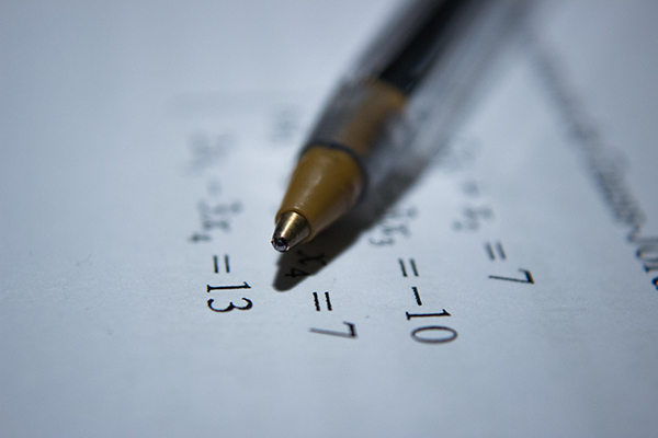 close up of a pen on paper with math sums