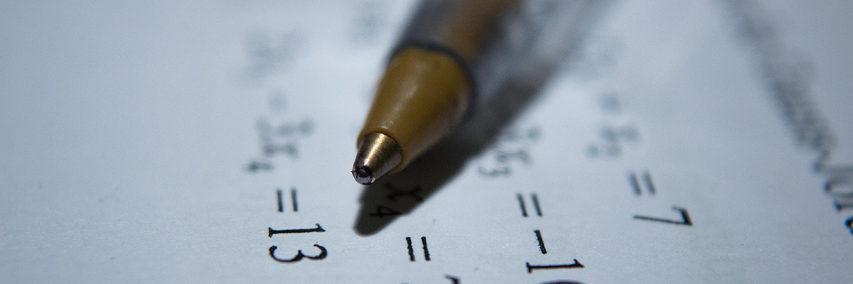 close up of math sums and a pen