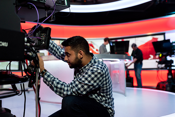 someone handling camera equipment in a TV studio