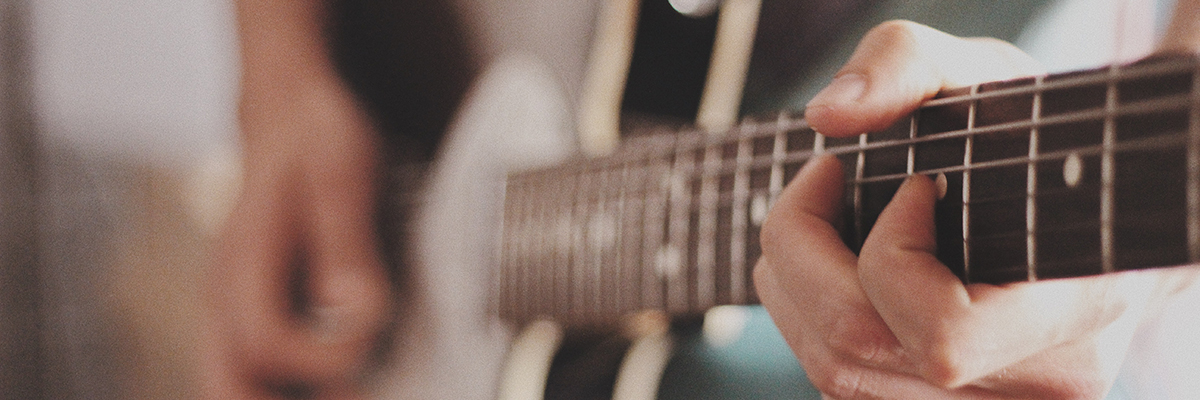 close up of someone strumming guitar