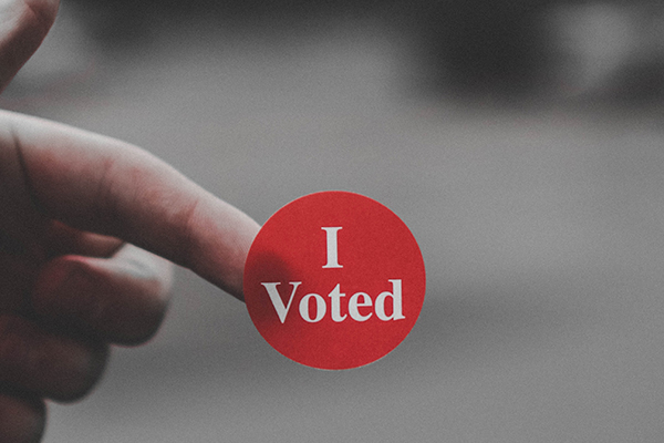 close up of someone holding a sticker that says 'I voted'