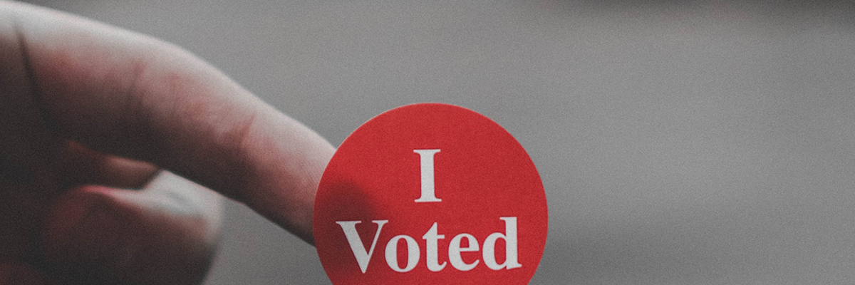someone holding a sticker that says 'i voted'