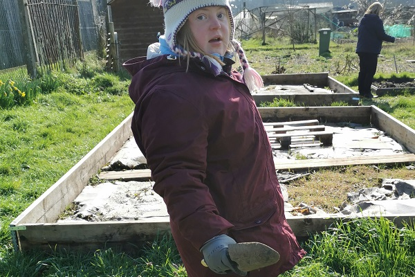 student holding a trowel in an allotment