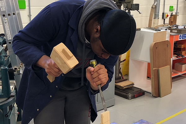 student in a workshop with a hammer