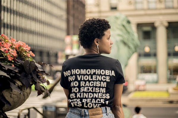a women wearing a t-shirt that says 'no homophobia, no racism, no violence'