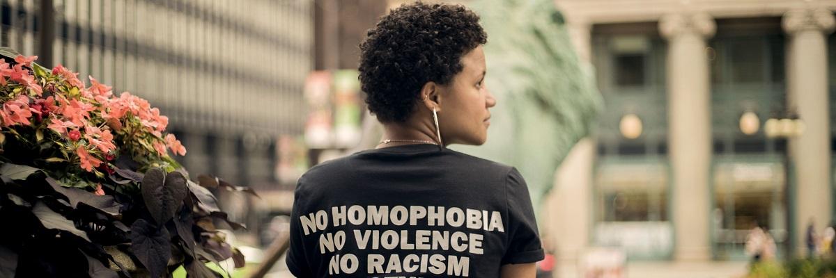 a women wearing a t-shirt that says 'no homophobia, no racism, no violence'