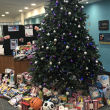donated gifts under a christmas tree in South Downs Campus reception