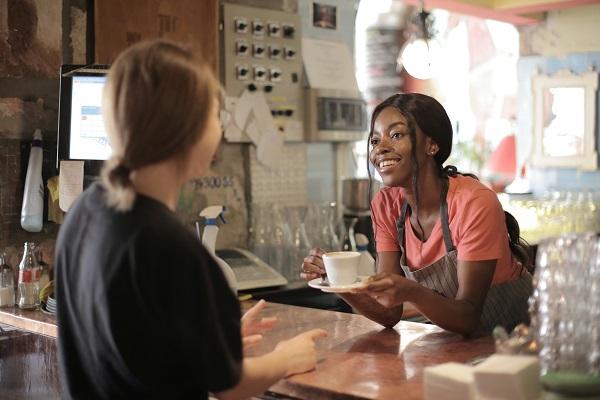 a women serving a customer their coffee