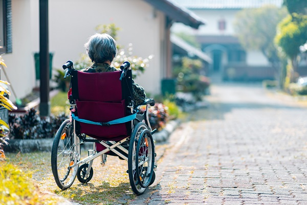 an elderly person sitting in a wheelchair looking into the distance