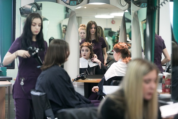 students in the college salon working on client's hair