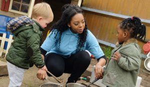 Childcare worker interacting with two young children