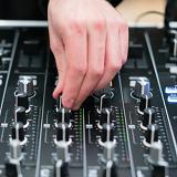 close up of a hand using a sound mixer