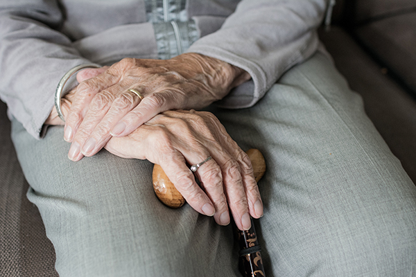a closeup of an elderly persons hands holding a walking stick