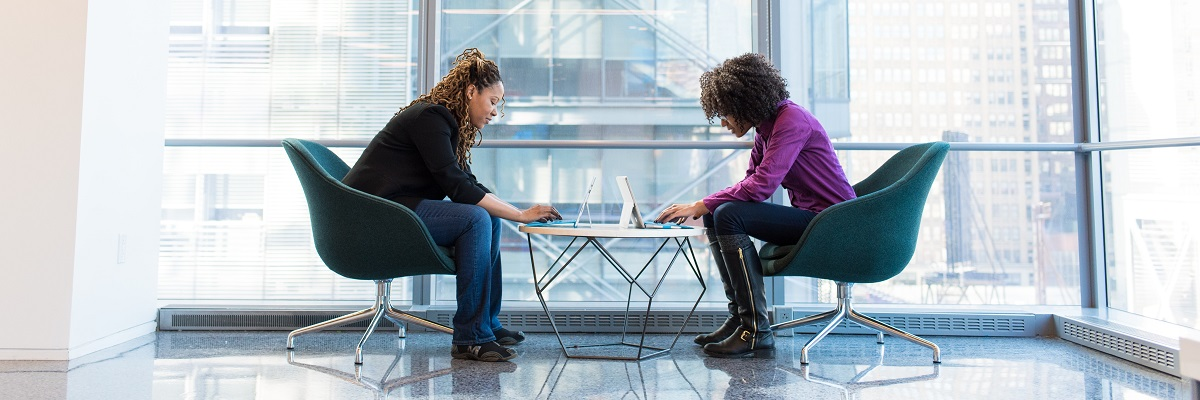 two women having a one to one meeting with laptops