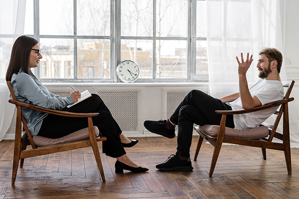 two people in a counselling session facing each other on chairs