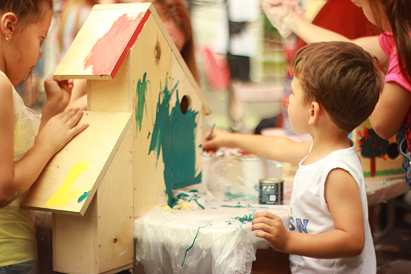 a child painting a wooden house