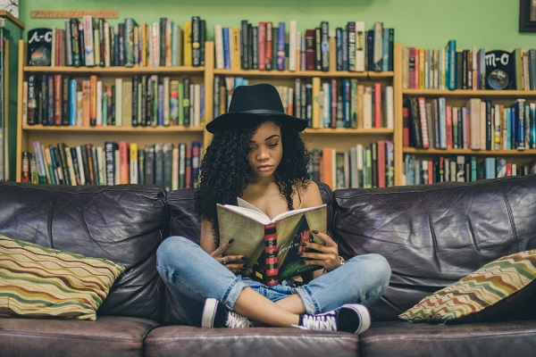 a female reading a book cross legged on a sofa with book shelves full of books behind her