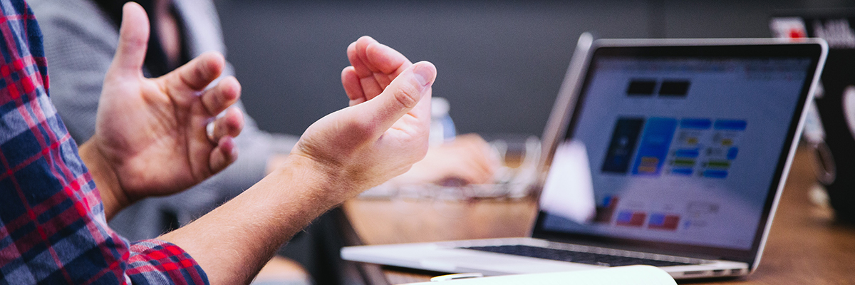 closeup of a mans hands in front of a laptop