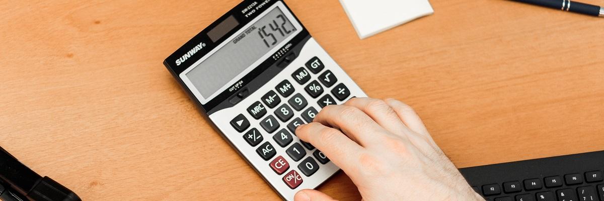 person using a calculator on a desk