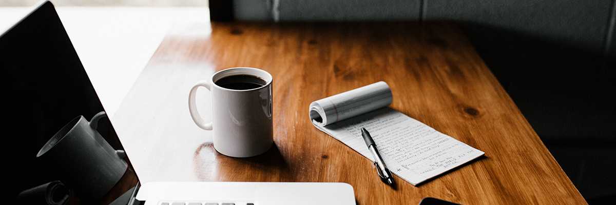 a notepad and pen, cup of coffee and laptop on a table