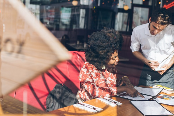 waiter helping a customer decide what food to order in a restaurant