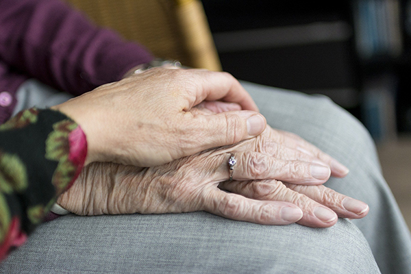 two elderly people holding hands