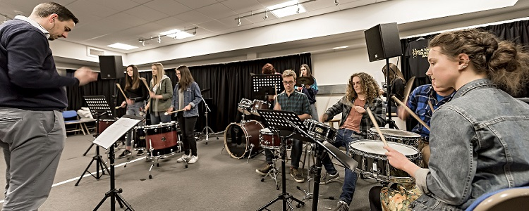 Students playing instruments with lecturer