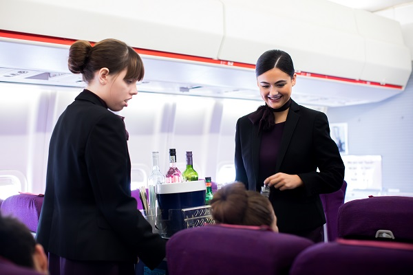two cabin crew students in the cabin serving drinks