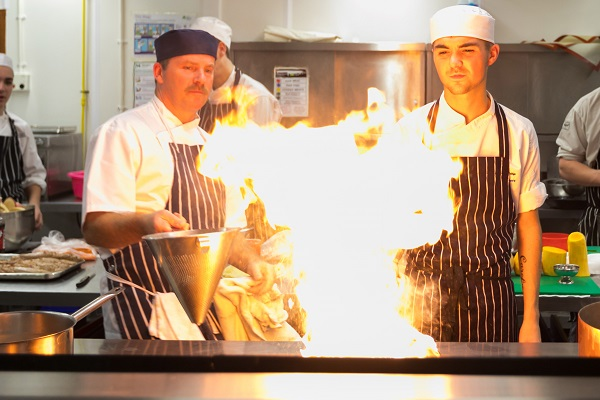 a student and lecturer cooking with fire