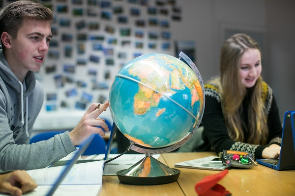 a student looking at a globe