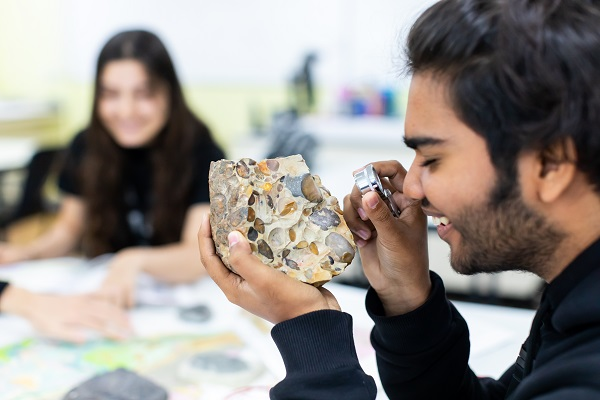 a student using a microscope to look at a piece of rock