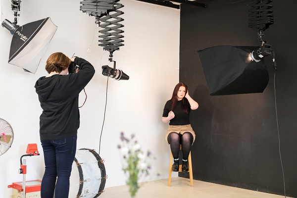a student in front of a photography screen with a student taking their photo with photography equipment