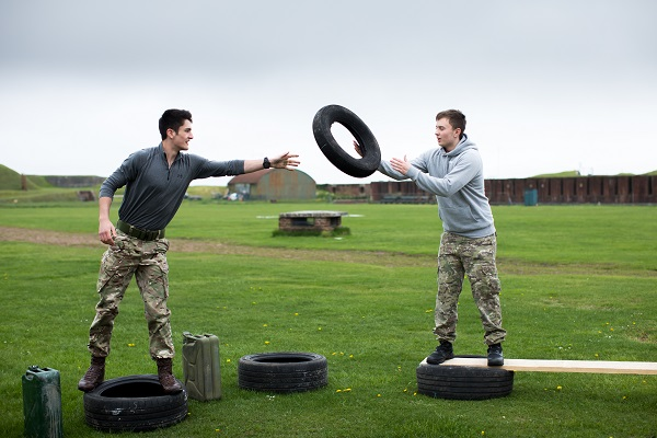 public services students outside participating in an activity passing tyres