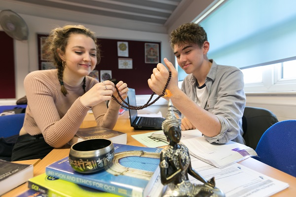 two students holding religious artefacts