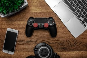 a ps4 controller, headphones, laptop and iphone on a desk