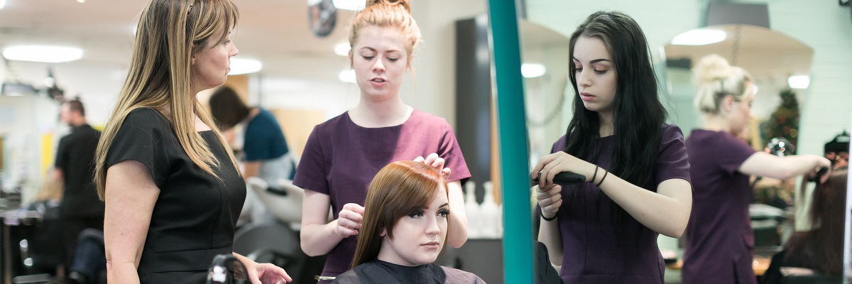 a student working on a client's hair in the college salon, with their lecturer