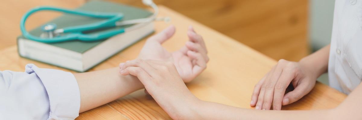 a nurse taking someone's pulse on their wrist