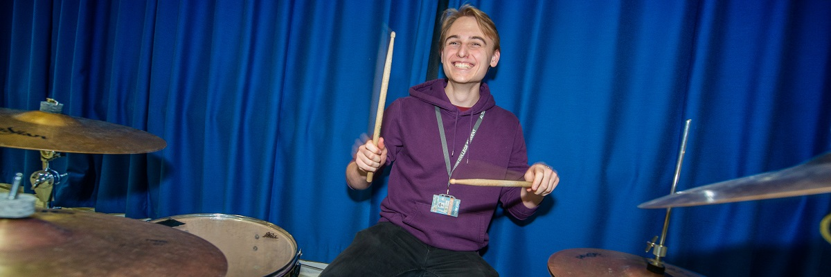 smiley male student playing a drum kit