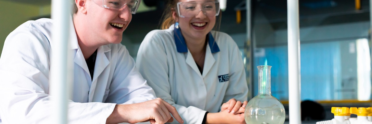 two students in science class in lab coats and protective eyewear, watching a chemical experiment and smiling