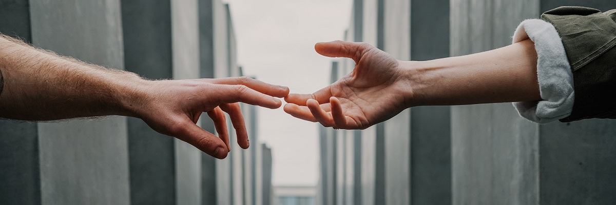 close up of two people reaching out to touch each others hands